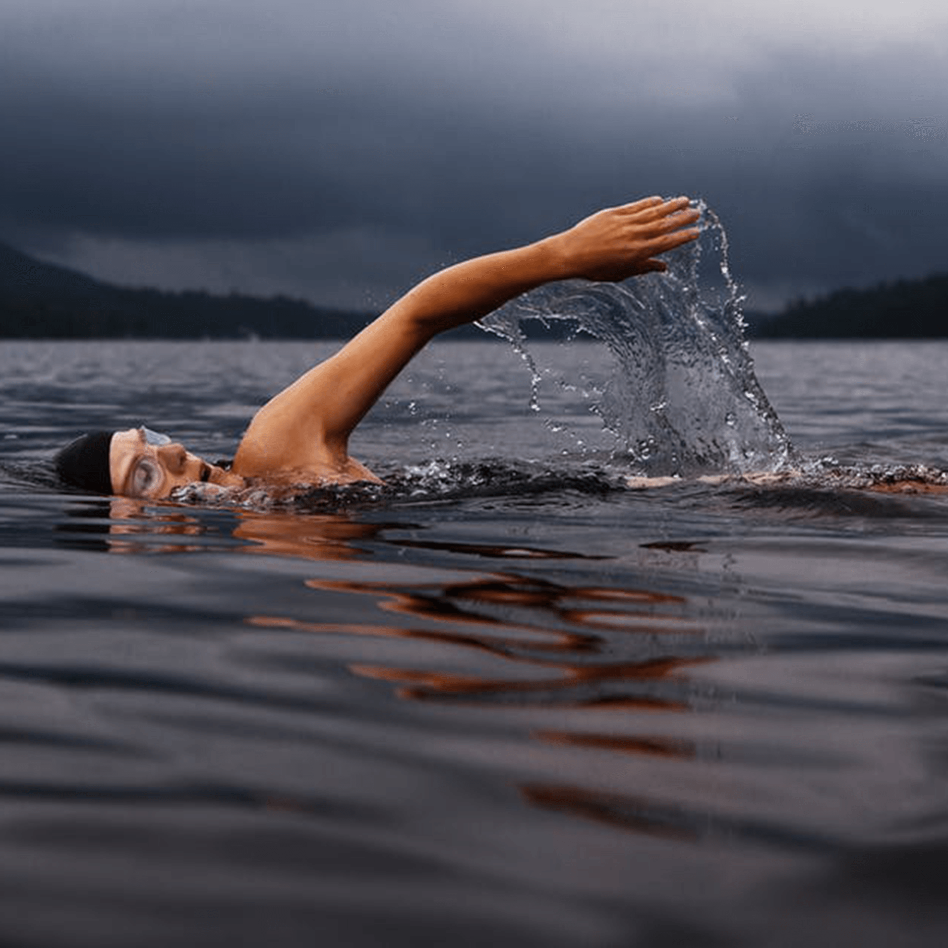 Swimmer wearing black bathing cap and goggle in a lake on a cloudy day.